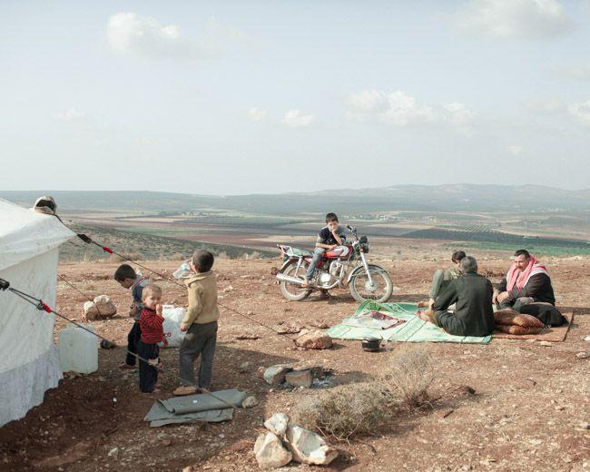 #SpeakUp4SyrianChildren   Déplacés syriens assis devant la frontière avec la Turquie, à côté de leur tente (Atmeh, octobre 2012)  photographie, Lorenzo Meloni