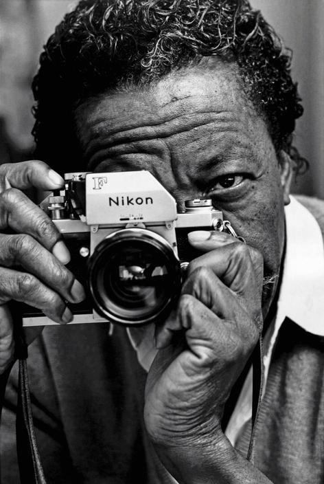 Photographer and director Gordon Parks looks through a Nikon camera.    1970