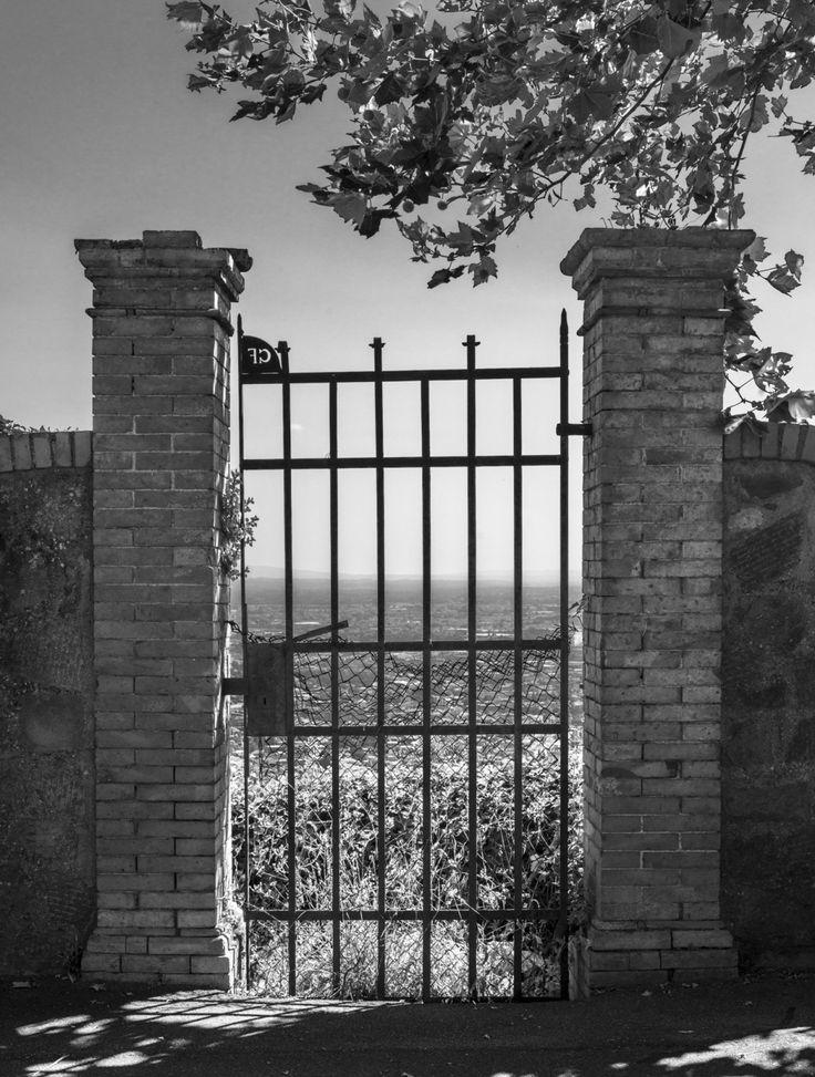 Lungo la strada che costeggia il poggio c'è questo vecchio cancello che sembra aprirsi sulla vallata.  Nonostante non fosse scattata pensando alla versione in bianconero, la versione a colori non era molto soddisfacente, e allora l'ho ridotta in toni di grigio.