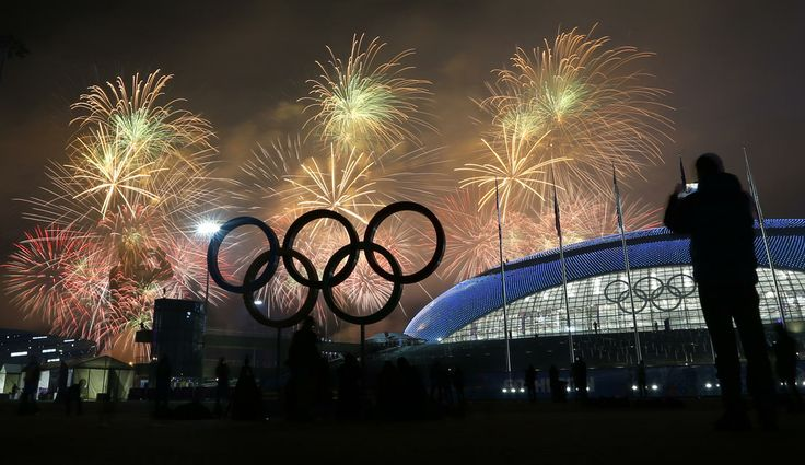 Man takes a photograph of fireworks during the closing ceremony of the 2014 Winter Olympics, Sunday, Feb. 23, 2014, in Sochi, Russia. (AP Photo/Petr David Josek)