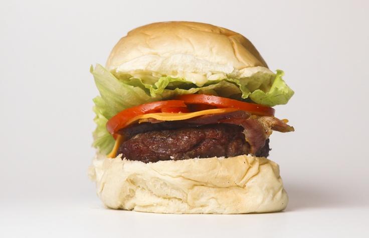 Hambúrguer de fraldinha com fatias de bacon e queijo cheddar.