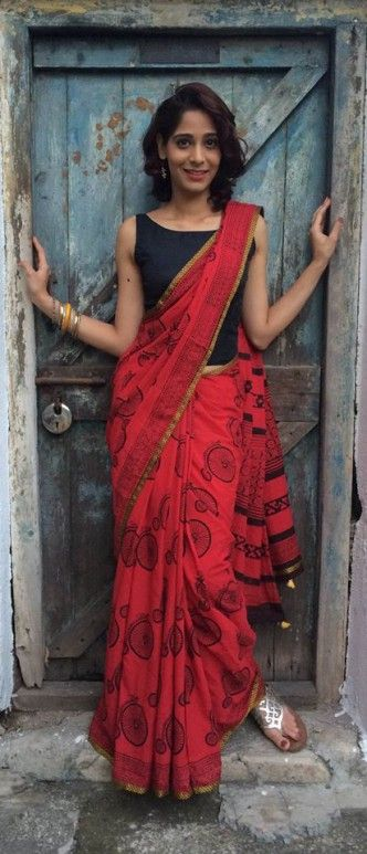 Red saree feat. a quirky cycle print pattern paired with a simple black blouse.