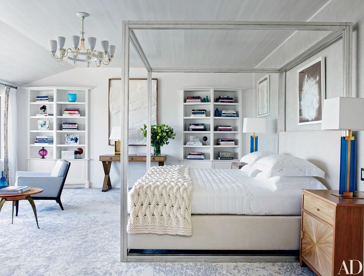A 1960 Paavo Tynell chandelier from Alexandre Biaggi crowns the master bedroom, which is furnished with a Larrea Studio canopy bed upholstered in a Bergamo fabric; the midcentury T. H. Robsjohn-Gibbings armchair is from Lobel Modern, and the '40s French low table is from Newel.