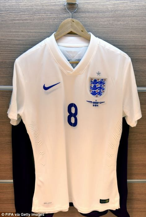 The shirt to be worn by Frank Lampard of England hangs in the dressing room before the match and the England emblem (right)