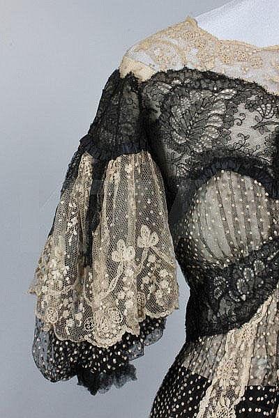 A black and ivory point d'esprit summer dinner gown, circa 1902, the gros grain waistband woven 'Raudnitz & Co, Huet & Cheruit Frs, 21 Place Vendome, Paris