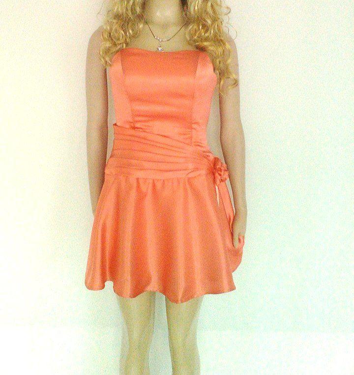 Vestido en satín color salmón, strapless, ajuste con corsé y falda rotonda.