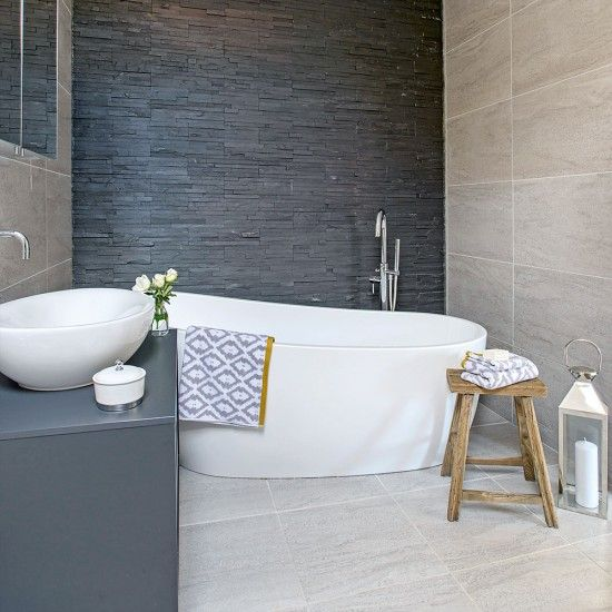 Slate clad bathroom with freestanding white slipper bath