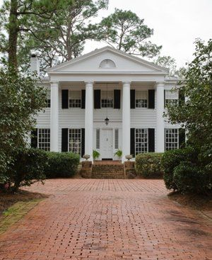 An alley of camellias frames the brick drive up to the Southern Colonial house. Elegant white columns highlight the classical architecture.