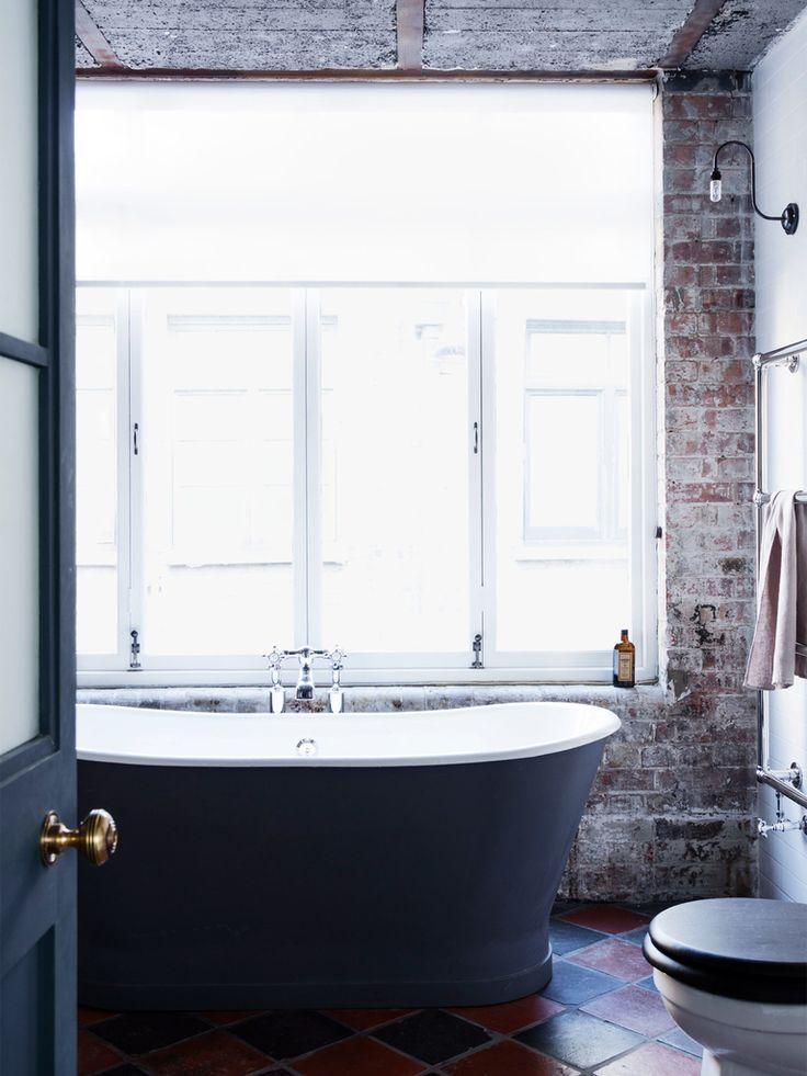 Отдельно стоящая ванна у огромного окна и станы из не оштукатуренного кирпича составляют колоритный интерьер.  (индустриальный,лофт,винтаж,стиль лофт,индустриальный стиль,интерьер,дизайн интерьера,мебель,архитектура,дизайн,экстерьер,квартиры,апартаменты,ванна,санузел,душ,туалет,дизайн ванной,интерьер ванной,сантехника,кафель,керамика,фото ванной,идеи ванной) .