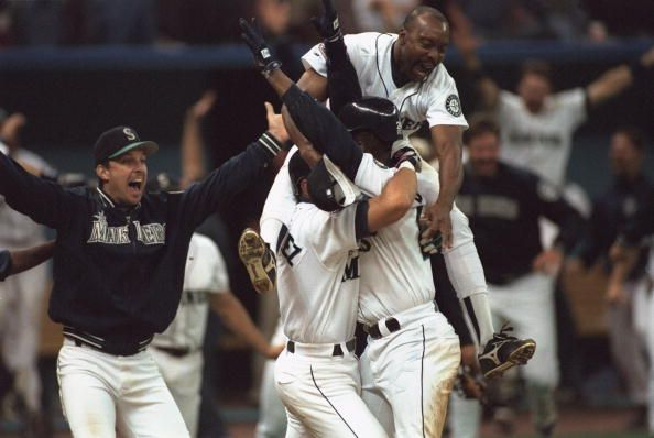 Baseball AL playoffs Seattle Mariners Ken Griffey Jr victorious with Alex Rodriguez and team after scoring game and series winning run vs New York...