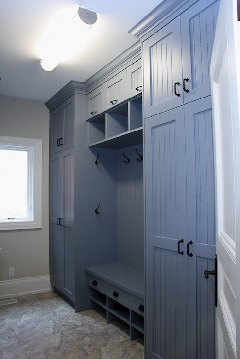 Blue Boot Room with floor to ceiling cabinets & beadboard trim doors. Boot Room also includes a built-in bench, hooks, and stone floors.