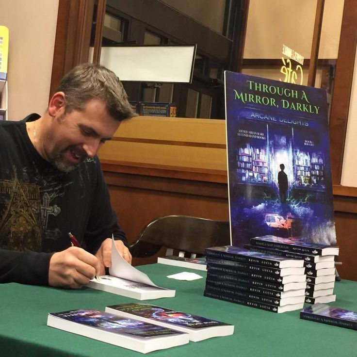 Kevin Lucia signing copies of his Through a Mirror, Darkly collection.