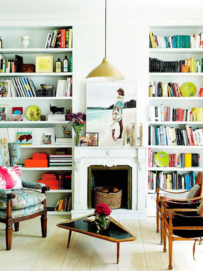 great living room with the folding Campaign chairs in wood/black and the patterned antique arm chair, fireplace, and colorful bookshelves :)