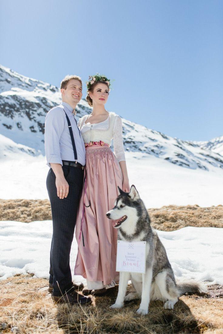 Brautdirndl in weiss mit Seidenschürze in altrosa. Brautpaar mit Hund auf einer Trachtenhochzeit. #dirndl  #tracht #hochzeit #brautdirndl #hochzeitsdirndl #winterhochzeit #almhochzeit #hochzeit