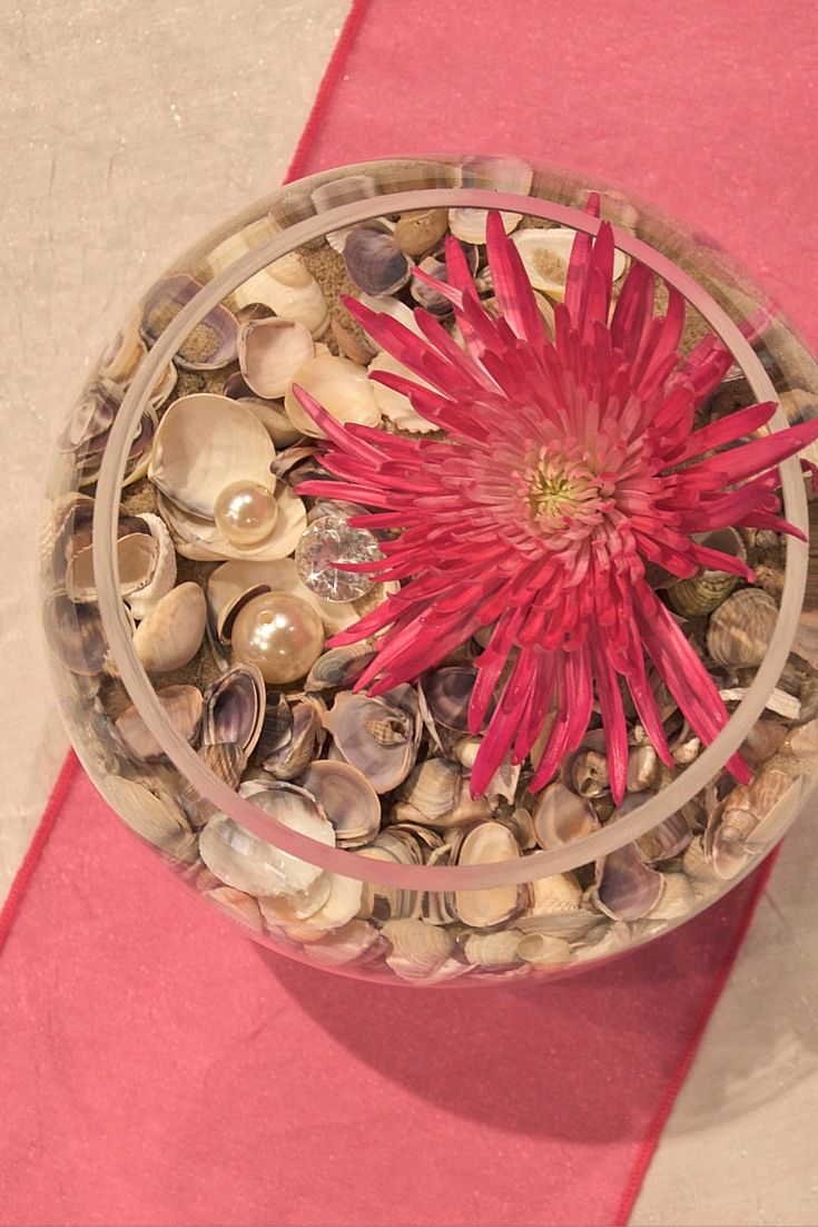 Simple Centerpieces incorporate our Under the Sea inspiration. Sand, shells, and pearls create a stunning bed for the simple fresh cut flower to rest. The white dazzle cloth and pink sash anchor this simple tablescape.