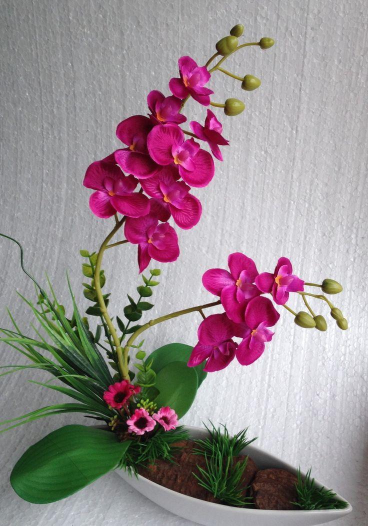 Vaso de orquídea artificial em fundo de porcelana branca, com grama artificial, cascas de árvores , criando um jardim.lindo!