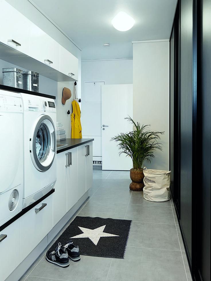 Et funktionelt bryggers med vaskemaskine og tørretumbler i ergonomisk højde. Bag skydelågerne er der seks kurve til vasketøj i forskellige farver, så tøjet allerede er sorteret inden vask.