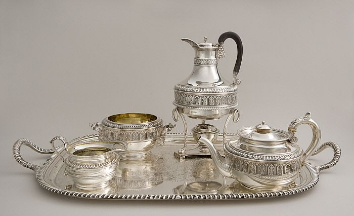 """Assembled Tea Service  by Paul Storr 1806 The sturdy, rounded shapes of the four vessels in this tea service—including a teapot, hot water jug, sugar bowl, and cream jug—were probably inspired by the forms of ancient Roman oil lamps. English silversmith Storr decorated several of the handles with acanthus leaves, a motif also adopted from classical antiquity. The service sits on an oblong tray, designed by Bennett, inscribed with the Latin motto facta non verba, meaning """"deeds, not words."""""""