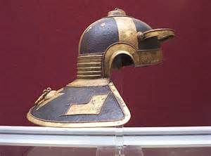 "The famous Niedermörmter Roman helmet of the 3rd century AD. Side view. This style of helmet with hinged cheek pieces and a large neck protection was found in the river Rhine (now in the Mainz museum). It is a Weisenau type. Along with the elaborate applique and perforated brow, this helmet sports a unique design element on the crown: what are described as either ""Mice and cheese"" or ""Mice and bread"". Some experts call this model the most beautiful Roman helmet."