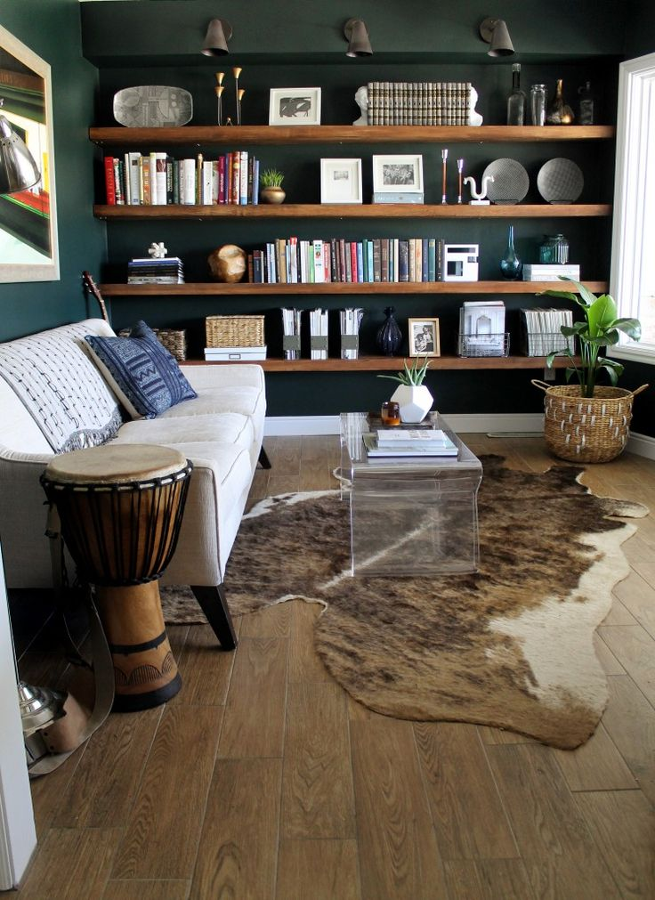 "Deep forest green on walls, wood wall-to-wall floating shelves, tribal feel of drum, tribal/kilim print on pillow, cowhide rug, ""wood"" floors, plant in basket"