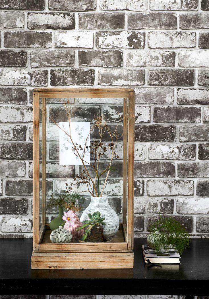 Behang Brick van vtwonen, per rol van 52 cm x 10 m (vtwonen.nl). Houten vitrinekastje (De Weldaad). Kleine vaasjes, grote vaas met streepjes (Maison NL). Overig privébezit.