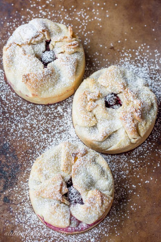 Mini Deep Dish Berry Pies dusted with confectioners' sugar, made with Black Raspberries and topped with vanilla ice cream.