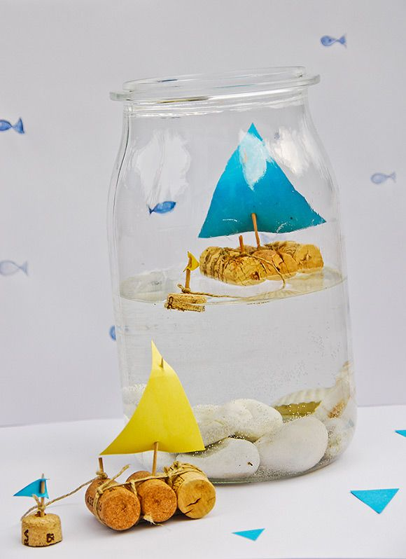 DIY Cork Sailboat In a Jar--How cute! All you need are corks, thread, tooth­picks and con­struc­tion paper.