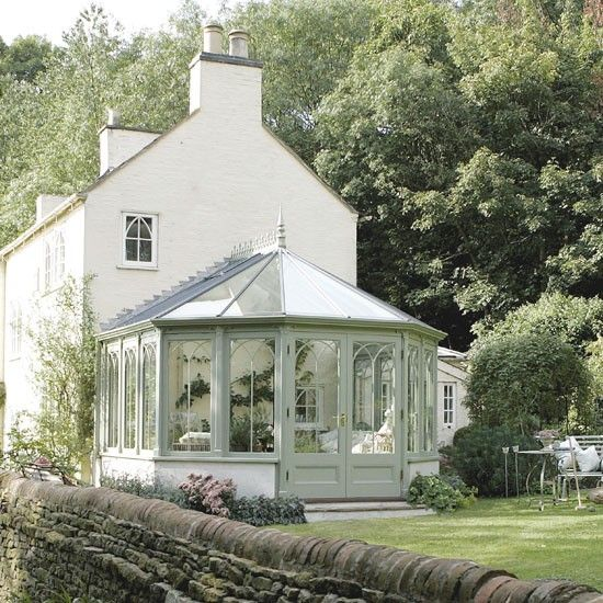 This bay-shaped conservatory, part of the National Trust collection, is painted in a shade of pale sage green, to fit harmoniously with its countryside setting. The classic design incorporates decorative scroll support castings and the framework has a stylish Victorian influence.