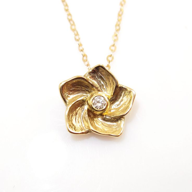 Flowering golden necklace with diamond Smaller series. A plump flower, inspired by the hibiscus, unfolds its petals and proudly displays a 0.05 TW / VVS diamond. The pendant is deliciously chubby and heavy - a real piece of quality jewelry!  Price without chain