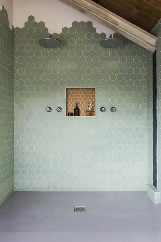 Not ready to renovate your floors? This gorgeous bathroom dabbles in the trend by gradually fazing out the hexagonal tiles towards the ceiling to make a honeycomb-like pattern. The best bit? You don't need to worry about matching the tiles with bespoke wooden panels so it takes a fraction of the time and effort.   Photo courtesy of Designs by Katy  #interior #design #tiletransitioning #bathroom #mydomaine