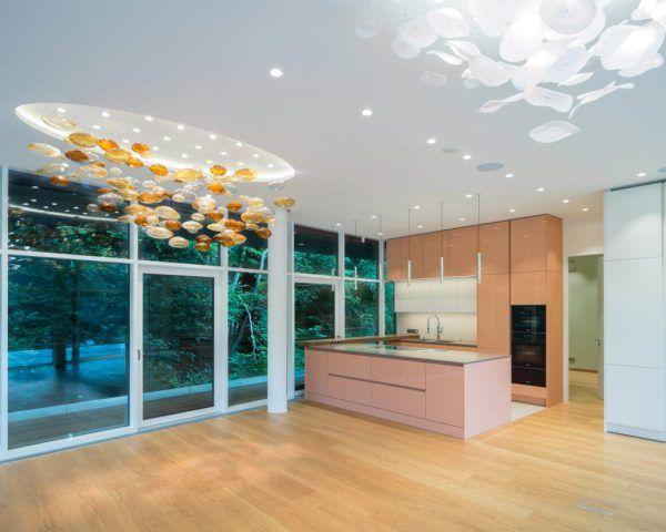 Design-Küche mit rosa (lachsfarbene) Fronten und zum Teil weißen Oberschränken und einer grauen Arbeitsplatte