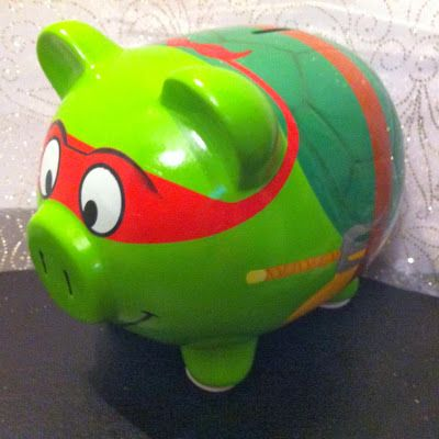 """Any of you out there, older or younger, remember waking up on Saturday and watching """"The Teenage Mutant Ninja Turtles""""? Now, you can always have that small piece of Saturday morning back (you know, pajamas and cereal days), each and every time you make a deposit into your TMNT piggy bank!"""