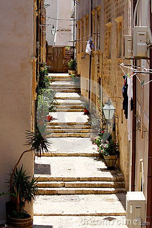 Bright old stairs on narrow pathway with stone buildings in Dubrovnik, Croatia.