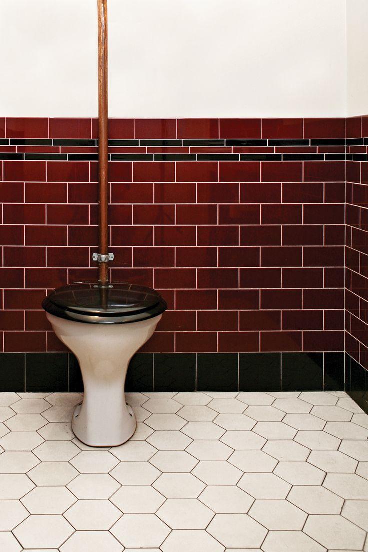 """Wc med högspolande toalett och tjugotalsinredning med rött kakel och svart bård. På golvet Victorian floor tiles """"Barcelona"""" helt i vitt."""