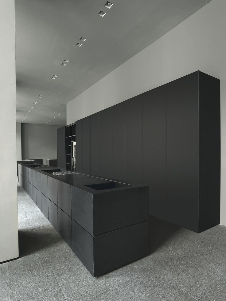 Beautiful minimal Minotti Cucine kitchen. matte black kitchen. black island bench lat black full height cupboards. simple
