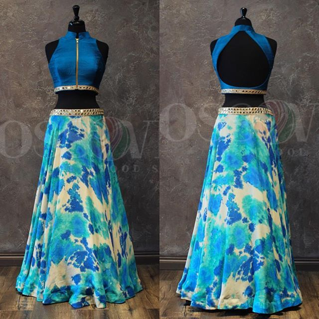 Summer Breeze This western style lengha comes with a tie-dyed skirt which has shades on blue and beige and a mirror work border. The top is done in a vibrant blue raw silk with a mirror work border, a front zipper and a keyhole in the back.