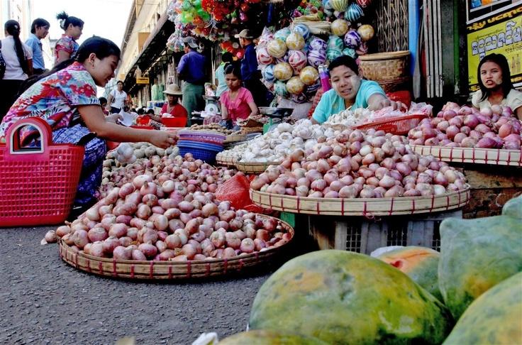 Women sell onions at a roadside market in Yangon