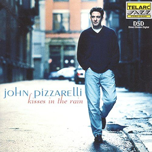 """Kisses in The Rain:   Kisses in the Rain by John Pizzarelli   Format: Audio CD. This is a diverse set of standards and original tunes that aims at the intimacy and spontaneity of John Pizzarelli's live performance with a studio setting. The singer-guitarist's long-established trio with pianist Ray Kennedy and brother Martin Pizzarelli on bass just keeps getting better, working with an instrumentation that Nat """"King"""" Cole first perfected in the '40s and which also served Oscar Peterson ..."""