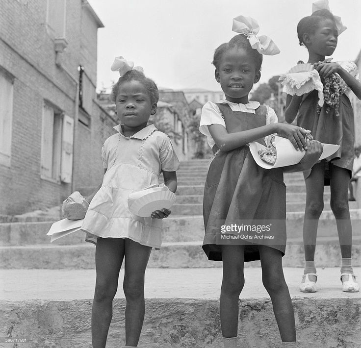 Three little girls pose in their school
