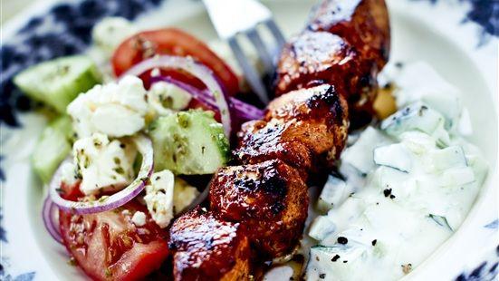 Putsa kycklingen och skär filéerna i 3 x 3 cm bitar. Marinera i marinaden minst 1 timme i kylskåp (gärna längre). Trä på spett, salta och grilla runtom ca 15 minuter. Blanda gurka, tomater och rödlök på ett fat. Smula över fetaost och smaksätt med olivolja, salt och peppar.   Servera kycklingspetten med fetaostsallad och tzatziki.