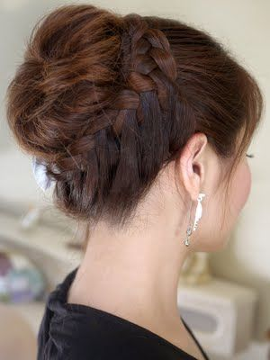 This is two ponytails-one on top of the head and one on the bottom. The top ponytail is teased and spun and pinned into a bun. The bottom ponytail is french braided side ways in the bottom area of the hair braided until it is wrapped around the first bun