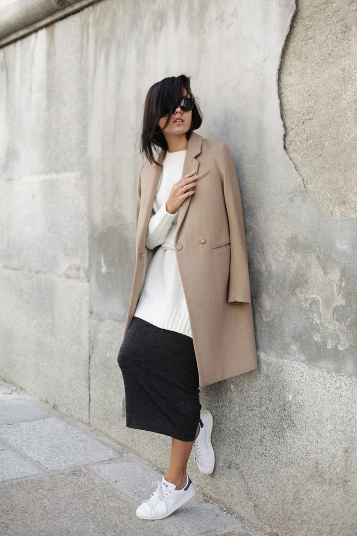 Opt for a camel coat and a charcoal midi skirt if you're going for a neat, stylish look. White canvas low top sneakers will add some edge to an otherwise classic look.   Shop this look on Lookastic: https://lookastic.com/women/looks/camel-coat-white-oversized-sweater-charcoal-midi-skirt/15171   — White Oversized Sweater  — Camel Coat  — Charcoal Midi Skirt  — White Canvas Low Top Sneakers