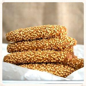 ΥΛΙΚΑ  360 ml ελαιόλαδο 400 γρ ζάχαρη ξύσμα ενός λεμονιού 120 ml φυσικό χυμό πορτοκαλιού 120 ml αλισίβα βρασμένη, κρύα (με 1 κ. σ. στάχτη) 40 ml ρακί ή κονιάκ 1 κ. σ. κανέλα σκόνη ¼ κ. γ. γαρύφαλλο σκόνη ½ κ. γ. αμμωνία ½ κ. γ. μαγειρική σόδα 600 γρ. (περίπου) αλεύρι μαλακό 400 γρ. σουσάμι