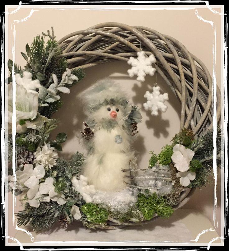 Ghirlanda con pupazzo di neve, fiori artificiali, muschio e fiocchi di neve di polistirolo.