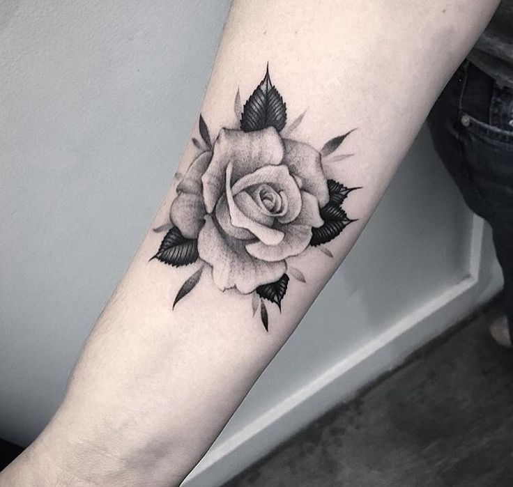 Black and white rose tattoo on forearm.