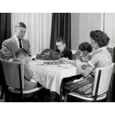 Mature couple with their children praying at a dining table on Thanksgiving Day Canvas Art - (18 x 24)