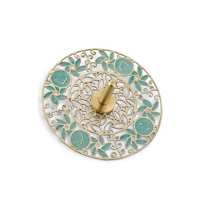This brass Dreidel is round in shape with a spinner attached to the center and features turquoise decorations, Hebrew text and cutout leaves and scrolling lines.