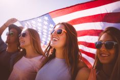 Cool teen friends smiling and holding an American flag stock photo