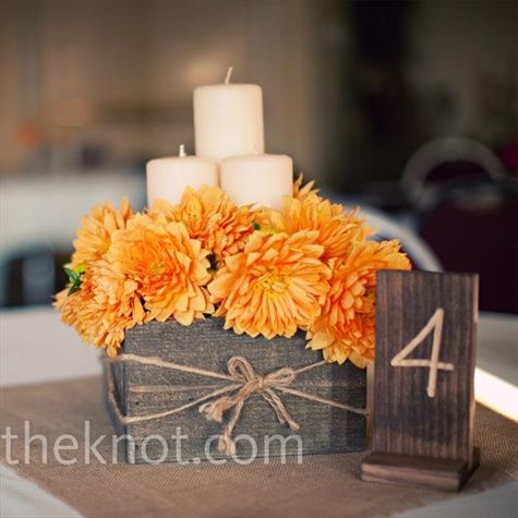 wooden boxes filled with either orange dahlias or red carnations and pillar candles of varying heights sit in the center
