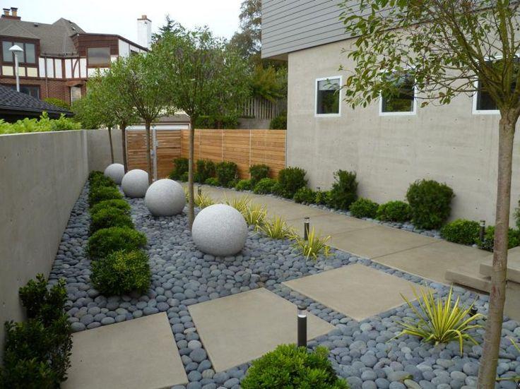 jardin moderne nécessitant peu d'entretien aménagé avec des buis en boule et décoré de galets gris